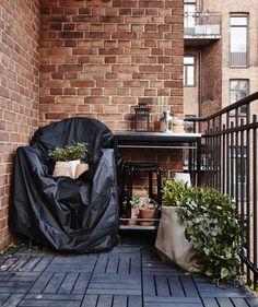 En altan i vinterhi med tildækkede stole og planter og lanterne opbevaret på et rullebord af metal.