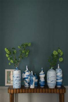 living room color ideas, dark ocean blue wall, wooden table with seven bottles with different shapes and sizes in different variations of blue, with green plants and a photo in a white frame