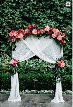 Les voilages sont mis en valeur par l'éclat des couleurs des fleurs pour une arche de cérémonie