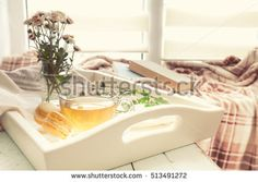 Cup of tea, books, chrysanthemum flowers and macaroons in tray on the table. Cozy home concept. Coloring and processing photo in vintage style.