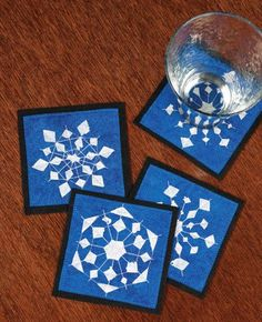 An adult version of paper snowflakes! Get instructions to make these snowflake coasters using freezer paper stencils and fabric paint. Easy DIY project to add some winter fun to your table.