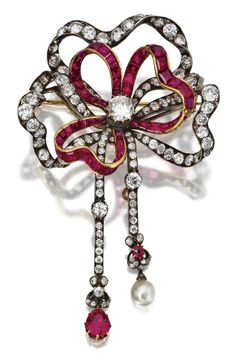 A Silver, Gold, Ruby, Diamond and Pearl Bow Brooch. Set in the centre with a round diamond, the bow and tassels set with old European-cut and rose-cut diamonds, the total diamond weight approximately 10.00 carats, accented by pear-shaped, cushion-shaped and calibré-cut rubies.