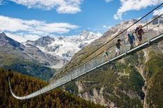 300 feet above an Alpine ravine, the Charles Kuonen Suspension Bridge forms part of the Europaweg — a two-day mountain trail which connects the towns of Grächen and Zermatt in Randa, Switzerland. Zermatt, Rando Velo, Places To Travel, Places To See, Pedestrian Bridge, Suspension Bridge, Swiss Alps, Wonders Of The World, Switzerland