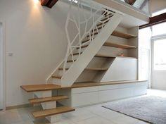 Escalier quart tournant avec marches en chêne. Garde-corps en acier découpé. Agencement sous escalier sur mesure, comprenant tiroirs et façade coulissante sur niche TV