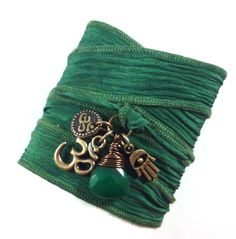 """Rock Pantone's color of the year - Emerald! This Om silk wrap bracelet features antique brass Om charms, hamsa, and genuine wire wrapped emerald jade briolette on a hand painted emerald green silk ribbon. -A hamsa possess magical powers of protection, happiness and prosperity. - Om is the Sanskrit letters or symbol for the """"sacred"""" Hindu sound om. This sacred symbol blesses people with luck, material comforts and spiritual powers. -Jade represents worthiness, lasting values, and long life."""