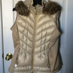 Michael Kors puffer vest Detachable hood with faux fur trim Sleeveless Zip front closure Two zipper hand pockets MK logo pulls on zippers Solid side panels Quilted allover Fill: down duck feathers Shell: Polyester / spandex / nylon / acrylic / modacrylic MICHAEL Michael Kors Jackets & Coats Vests