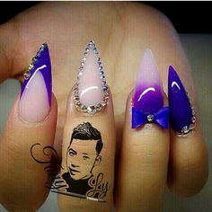 Purple stiletto nails with gems and a accent bow