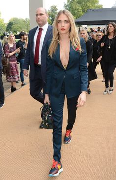 Cara Delevingne steps out in a sleekly bare midnight-colored suit with sporting touches in shades of poppy.