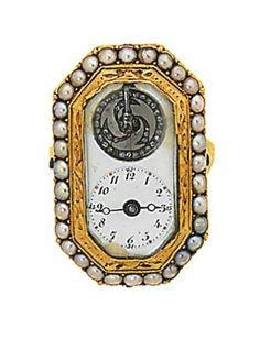 A rare early 19th century gold and half-pearl watch ring   The octagonal bezel with white enamel dial and black Arabic numerals and aperture revealing the rose-cut diamond balance wheel to the cylinder movement, within a half-pearl line and engine-turned border, the reverse with sliding plate revealing the key positions for the movement, hands and advance and retard, French or Swiss, circa 1810