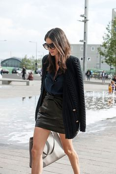 Leila Yavari street style in London with leather skirt and cardigan.
