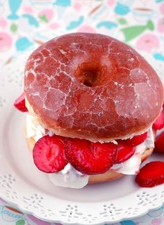 A glazed strawberry donut cut in half and filled with whipped cream a fresh cut strawberries!