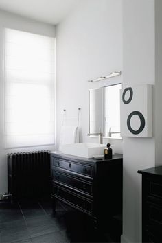 antique dresser painted black with modern sink attached