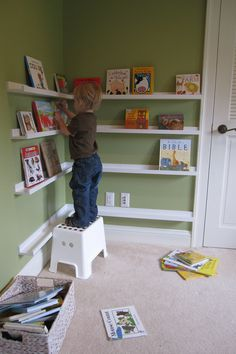 This is the new bookshelf in L's bedroom. Our handyman cut and mounted some IKEA photo ledges for us.