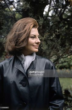 Close-up of Princess of Iran Soraya (born Soraya Esfandiary-Bakhtiari), the second wife and Queen Consort of the late Shah of Iran, in a sensual pose, next to a bunch of long stem red roses in her house in the Appia Antica. Rome (Italy), 1964..