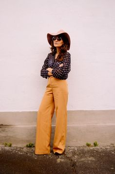 25 Chic and Simple Ways to Take Your Wide-Brim Hat Into Spring - mustard yellow wide leg trousers, a polka dot blouse, and a floppy wide-brim hat—70s inspired perfection.