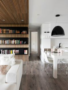 I like how they deprecate the dining and living space through different materials (wood wall and ceiling over living). Good way to divide open plan