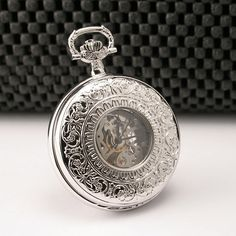 Sterling Silver Mechanical 3751: This 17 jewel pocket watch from Charles Hubert has a 17 jewel mechanical movement. Features a sterling silver dust cover and case backing. The front cover has a window so you can see the time without opening the cover. Ornately carved on the front and back with a floral motif. Case diameter is 1.8 inches and the thickness is .6 inches. Weight 2.8 ounces. Chain and gift box included.