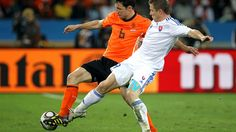 DURBAN, SOUTH AFRICA - JUNE 28: Juraj Kucka of Slovakia tackles Mark Van Bommel of the Netherlands during the 2010 FIFA World Cup South Africa Round of Sixteen match between Netherlands and Slovakia at Durban Stadium on June 28, 2010 in Durban, South Africa. (Photo by Doug Pensinger/Getty Images)