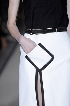 Angled pocket & thigh-high split with black trim; monochrome fashion details // YSL