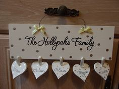 Handmade Decorations 10.00. A gift idea by Tracy Littlewood found on MyOwnCreation.co.uk: A beautiful wooden family plaque, hand painted in the colour of your choice, featuring any hand written surname. Personalised with five hanging hearts with your selected names. Embellished with ribbon bows and ready to hang with twisted wire. These signs make an excellent gift!