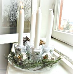 This year's Advent candles! Made from a glass plate decorated with fir and cedar, silver Christmas balls, pine cones and little silver stars. The candles are held in shot glasses stuffed with white linen.