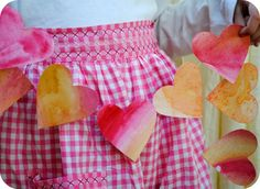heart garland - paint paper with water color in shades of red, pink, yellow, and orange, let dry, then cut out hearts and tape to string