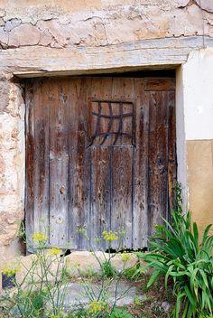 Negrón. Puerta antigua con ventanuco de diseño