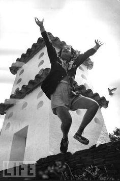 """Salvador Dali cavorts on a rooftop at his home in Cadaques in 1955 by Charles Hewitt.  Salvador Dali saltando en el tejado de su casa en Cadaqués.  El que quiere interesar a los demás tiene que provocarlos"""" S. Dalí."""