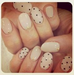 Nude or cream coloured nails with sporadic black polka dots