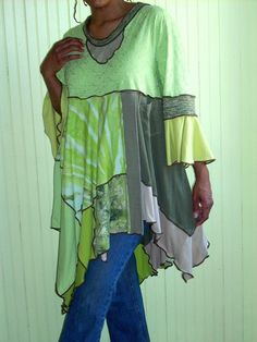 This rich tunic is a beautiful mix of colors and textures in a watercolor finish of chartreuse, olive and lime green. It is styled with a low collar neckline and flutter sleeves on an embroidered empire bodice .The overlapping bottom is a flared silhouette with contrasting patched fabrics and ends with an asymmetrical hemline. It is made entirely of repurposed t-shirts. All the seams are stitched then the edges serged throughout in decorative contrasting thread. This piece is carefree…