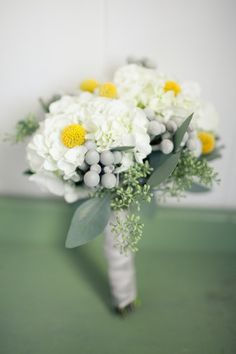Possible bridesmaids bouquets of cream hydrangeas, green seeded eucalyptus, grey dusty miller, ivory balsa wood flowers, yellow craspedia, and silver brunia wrapped in slate grey ribbon.