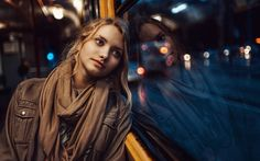 girl looking out of window bus on city street bokeh lights winter. The girl looking out the bus window sadly when going home in the winter rainning night