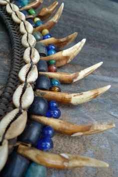 Borneo   Details from an antique Bidayuh elders necklace, adorn with several authentic teeth, seashell and priceless Lukut Sekada antique beads, each of these secured with wire and rattan.    Circa 1940.