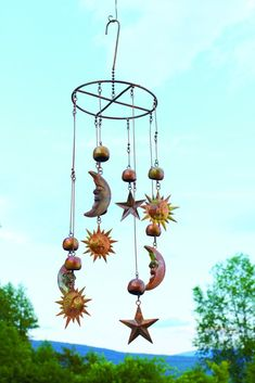 Flamed Sun, Moon, Stars Mobile accented with small bells, which provide a soft, pleasing chime as the mobile moves with the breeze. This handcrafted garden mobile will perfectly accent your outdoor space. #gardendecor #gardening #mobile #windchimes #sunmoonstars #gardens #outdoor