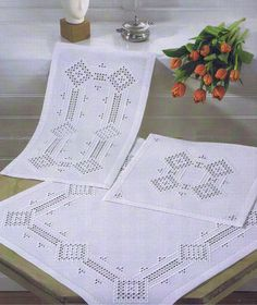 Crisp white table mats with hardanger diamonds joined by bars.
