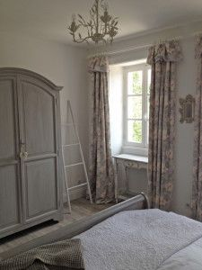 White walls, french painted furniture and light flooding in from two big windows, make this the perfect bedroom for a holiday home