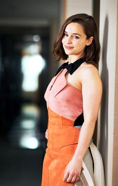 Emilia Clarke blushly smiling in sleeveless sheath dress w/ lapeledblsuh chest, pumpkin skirt, black straps w/ dark chocolate lob