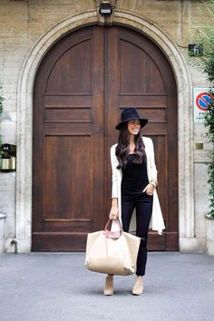 An all-black traveling outfit is simple and chic. Throw on a long cardigan to cozy up in on long-haul flights and a cute hat to conceal second- (or third-) day hair. Take a cue from frequent traveler Kat of With Love From Kat, and finish the look with booties that are easy to slip on and off.