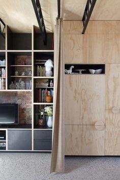 Hello House by OOF! Architecture. Panneau plein de contreplaqué et contraste du bois clair et des étagères sombres.