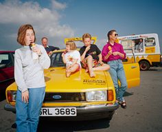 A family eating ice-cream around a parked yellow car, Image from Martin Parr's series From A to B, A Tale of Modern Motoring, 1994. Now on view at Autophoto Paris
