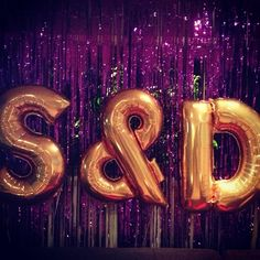 "Giant 40"" gold letter balloons in our initials. Sitting in front of a purple foil curtain. It was the talk of the Engagement party!"