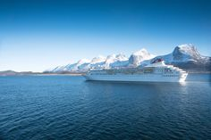 Fred. Olsen Cruise ship Braemar sailing past The Seven Sisters - mountain range on the island of Alsten in Norway