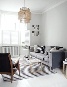 Light scandi living room with painted white floors, light grey walls in Farrow & Ball Blackened and a simple grey IKEA sofa