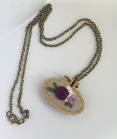 One hand embroidered floral Necklace, comes with bronze plated necklace. Ready to wear and ready to ship!  These are a great gift for someone on their birthday or lovely handmade gift for Mothers Day. Maybe you want to treat yourself .... guaranteed to be unique as I dont generally make the same thing over and over.   Necklace Details: • Size: Oval 4.5cm x 2.7cm • Comes with 70cm bronze plated necklace • Wooden Mini Frame Setting • As is the nature of handmade, no two pieces are exactly the…