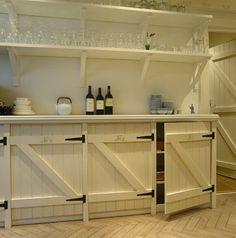 Shelves used to store wineglasses are mounted above a row of kitchen cupboards designed to resemble stable doors. Photographer: Fritz von der Schulenburg/The Interior Archive Designer: Mimmi . Cottage Kitchen Cabinets, Kitchen Cupboard Designs, Kitchen Ideas, Pallet Kitchen Cabinets, Kitchen Trends, Barn Door Cabinet, Kitchen Cabinet Doors, Diy Cupboard Doors, Kitchen Shelves