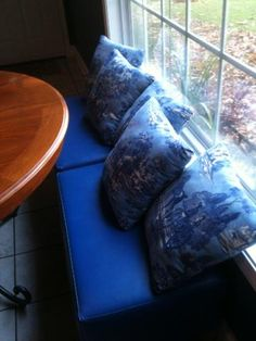 """Blue """"faux"""" Window seat I created using blue ottomans and lots of pillows I sewed up.  Love the blue in my kitchen!!!"""