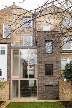 A brick tower and a glass volume form an extension by Gundry & Ducker to the rear of this London residence, creating a kitchen with garden views
