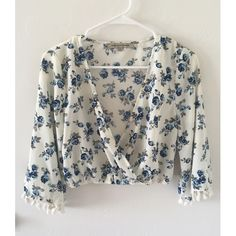 Floral Tassel Crop Top A longer sleeved crop top that has tassels on the sleeves and a blue and creme floral pattern that draped on the front. Only worn once. No signs of wear or tear. I bundle, just ask or use the bundle feature!  Foreign Exchange Tops Crop Tops