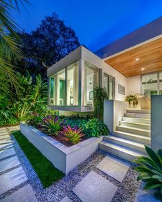 Simple concrete pavers and gravel line the walkway to the entrance of this modern subtropical home. The planter at the base of the large glass window is beaming with tropical plants.