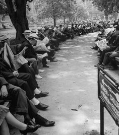 Benches lined with people reading newspapers with headlines of the D-Day  invasion; in Pershing Square Park, Los Angeles, California.